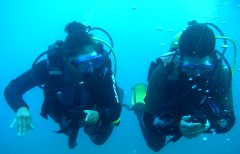 Two divers compare the direction as they practice navigating underwater in Gran Canaria